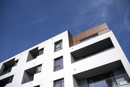 Exterior of new apartment buildings on a blue cloudy sky background. No people. Real estate business concept.