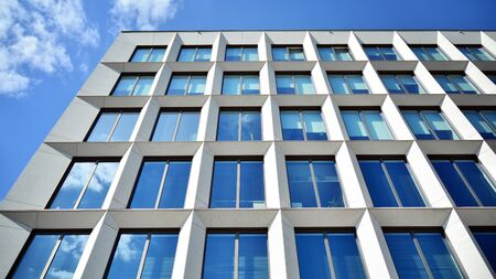 Modern office building windows with vertical lines and reflection. Building reflecting the sky with clouds and creating a surreal view.