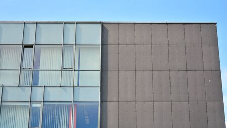 Glass building with blue sky background. Modern office building detail, glass surface clouds reflected in windows of modern office building. Stock Photo