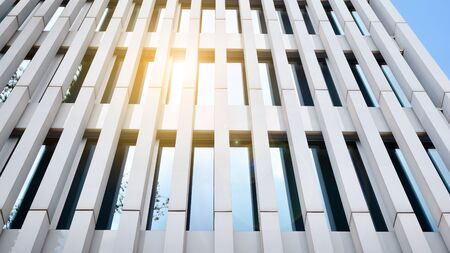 Modern architecture with sun ray. Glass facade on a bright sunny day with sunbeams on the blue sky.