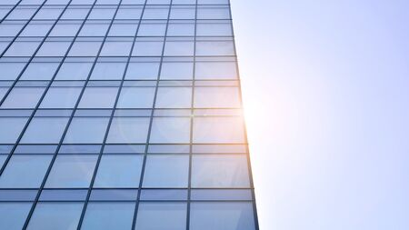 Bottom view of office building window close up with sunrise, reflection and perspective. Modern architecture with sun ray. Glass facade on a bright sunny day with sunbeams on the blue sky. Stock fotó