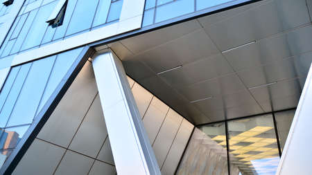 Combination of metal and glass wall material. Steel facade on columns. Abstract modern architecture. High-tech minimalist office building. Contemporary business architecture abstract fragment.