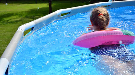 Child girl inside a blue swimming pool in summer. Child and having fun in swimming pool. 版權商用圖片