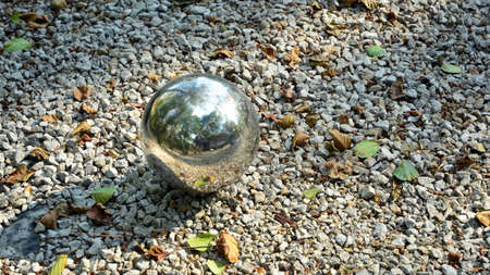 Shiny, decorative metal ball in the garden Imagens