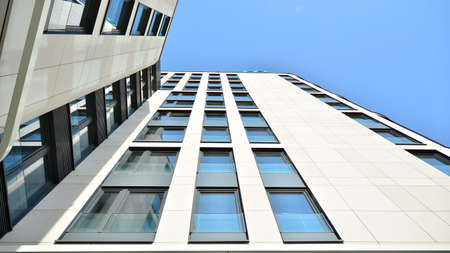 A fragment of the sandstone facade of a modern office building. Wide abstract fragment of modern building facade. 免版税图像