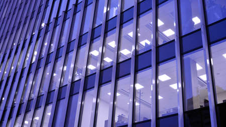 Pattern of office buildings windows illuminated at night. Lighting with Glass architecture facade design with reflection in urban city. Archivio Fotografico