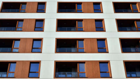 Facade of new apartment building. Glass balcony and clean look of modern architecture building with blue sky background. Stok Fotoğraf