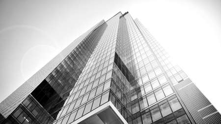 Bottom view of modern skyscrapers in business district against sky. Looking up at business buildings in downtown. Rising sun on the horizon. Black and white.
