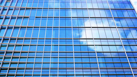 Abstract closeup of the glass-clad facade of a modern building covered in reflective plate glass. Architecture abstract background. Glass wall and facade detail. Velvia graphic filter. Stock fotó