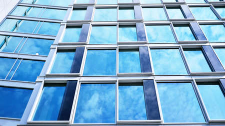 Abstract closeup of the glass-clad facade of a modern building covered in reflective plate glass. Architecture abstract background. Glass wall and facade detail. Velvia graphic filter.