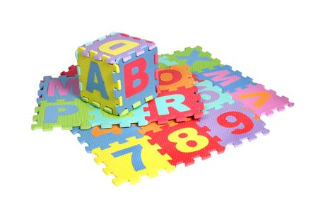 pedagogic: Bright colourful puzzle mats with matching spaces for letters and figures on white background. Clipping path included. Stock Photo