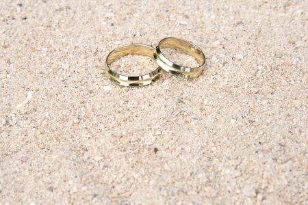 gold rings: A pair of gold wedding rings delicately placed in the sand on a tropical beach Stock Photo