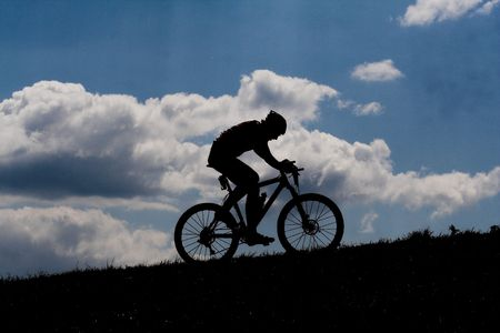 bycicle racer silhouette with clouds in the background