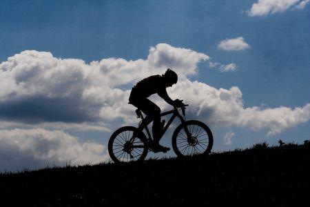 en mont�e: silhouette de coureur de bicyclettes avec nuages en arri�re-plan Banque d'images