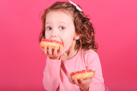 Baby girl eating donuts over pink background in room. Unhealthy lifestyle. Archivio Fotografico