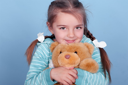 Smiling child girl holding teddy bear over blue Stock Photo