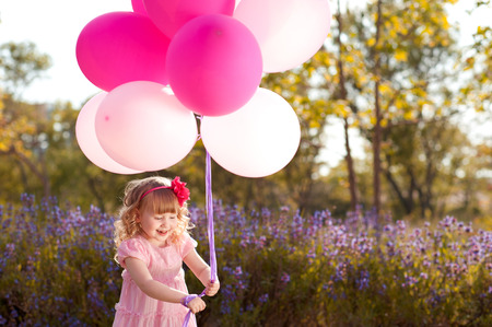 childrens: Kid girl playing with balloons outdoors