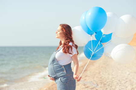 Pregnant woman resting at beach. Holding air balloons outdoors. Relax. Motherhood. Archivio Fotografico