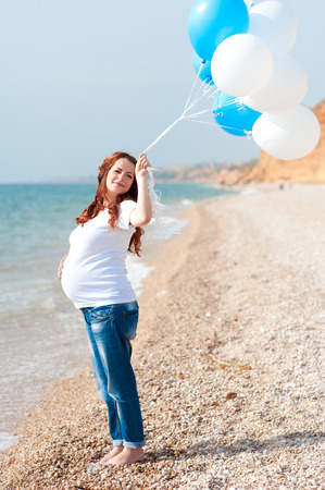 Happy pregnant woman playing with balloons outdoors. Resting at sea shore. Motherhood.