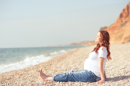 Pregnant girl sitting at beach resting. Summer time, Wearing casual clothes. Motherhood.Maternity. Prenatal. Archivio Fotografico