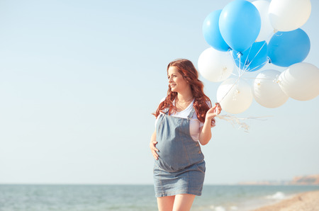 Pregnant woman holding air balloons outdoors. Walking at seashore. Motherhood. Maternity. 스톡 콘텐츠