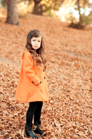 Kid girl 4-5 year old wearing stylish coat and knitted hat in park. Standing outdoors. Looking at camera. Childhood. Stock Photo