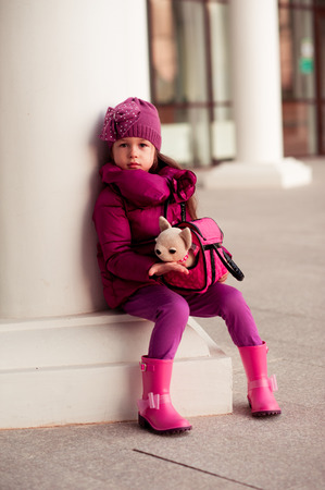 young girl: Baby girl 4-5 year old holding bag with toy dog outdoors. Wearing stylish pink winter jacket.Looking at camera. Childhood.