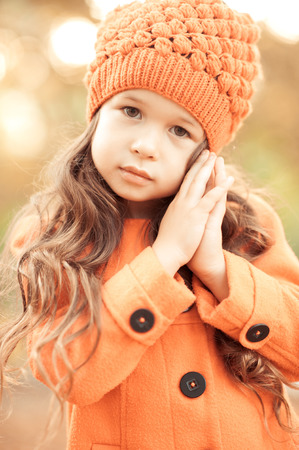 mignonne petite fille: Cute child girl 4-5 year old wearing stylish coat and knitted hat outdoors. Posing in park. Looking at camera. Seasonal. Childhood. Fashionable kids. Open air.