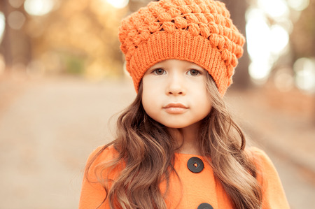 seasonal clothes: Closeup portrait of cute baby girl wearing knitted hat and winter jacket outdoors. Looking at camera. Childhood. Seasonal. Stock Photo