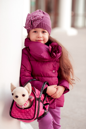 34: Smiling baby girl 3-4 year old holding toy pet in bag outdoors. Looking at camera. Wearing trendy winter jacket. Childhood.