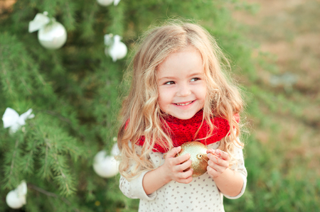 Funny baby girl wearing knitted scarf and shirt holding glitter christmas ball standing over christmas tree outdoors.Looking at camera. Posing outdoors. Holidays time. Childhood. 写真素材