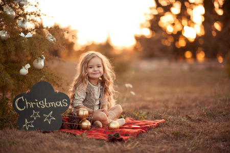 Cute child girl 4-5 year old sitting with christmas decorations outdoors. Looking at camera. Playful. Celebration. Childhood.