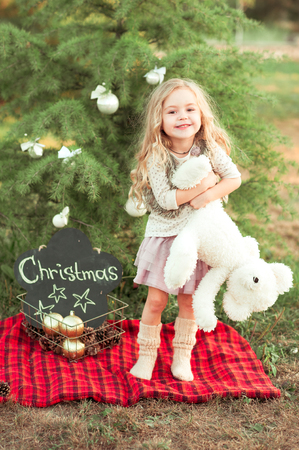 Smiling child girl 4-5 year old wearing knitted hat and scarf holding christmas decor outdoors. Christmas tree with decorations. Holiday time.