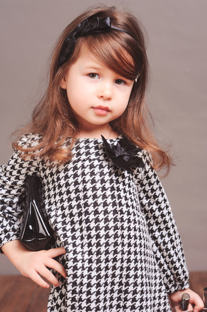 hairband: Stylish kid girl 4-5 year old wearing trendy dress, holding black leather bag and hairband. Looking at camera. Young model.