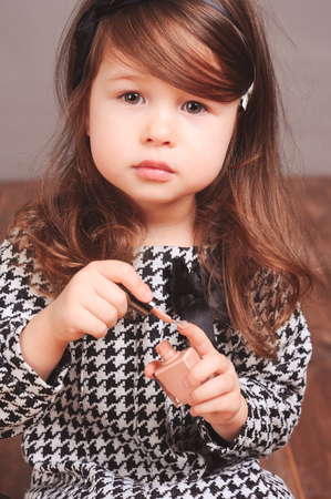 34: Adorable kid girl 3-4 year old playing with makeup products in room. Looking at camera. Stock Photo