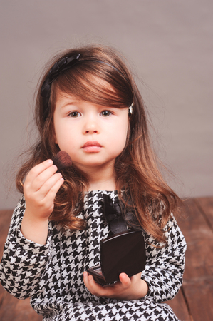 powder room: Beautiful baby girl 3-4 year old applying powder on face in room. Looking at camera. Wearing stylish dress.