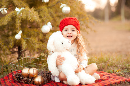 children clothing: Laughing kid girl 5-6 year old playing with white teddy bear outdoors. Christmas decorations. Celebration. Playful. Looking at camera.