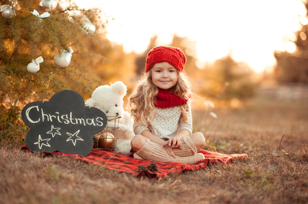 celebrate: Cute kid girl sitting with christmas decorations outdoors. Wearing red knitted hat and scarf closeup. Celebrating christmas at meadow. Christmas tree decor. Smiling child. Merry christmas. Childhood.