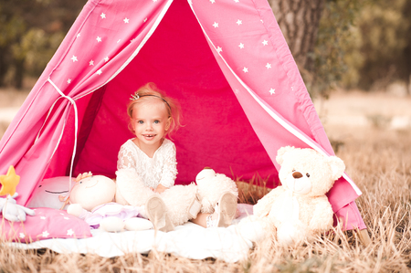 Cute baby girl 2-3 year old sitting playing with toys at back yard outdoors Stock Photo