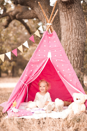 wigwam: Smiling kid girl 2-3 year old playing in wigwam outdoors. Looking at camera. Childhood. Stock Photo