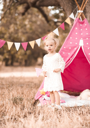 Smiling child girl celebrate first birthday outdoors. Looking at camera. Childhood.