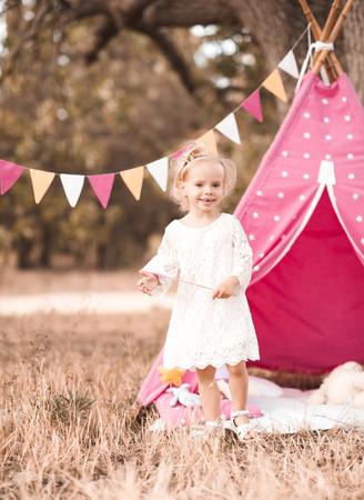 wigwam: Happy kid girl 2-3 year old playing over wigwam outdoors
