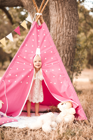 Laughing baby girl playing in wigwam with toys outdoors. Looking at camera. Playful Stock Photo