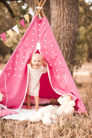 Laughing kid girl 1-2 year old playing in wigwam outdoors. Looking at camera. Childhood. Stock Photo