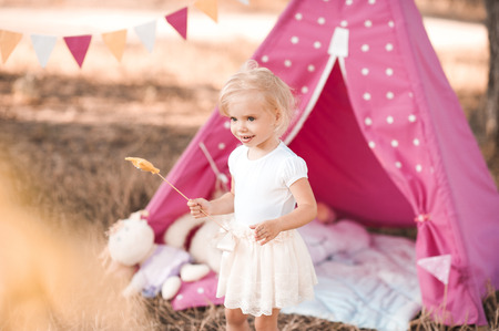 Smiling baby girl wearing white skirt and summer top playing outdoors with wigwam. Birthday party. Childhood.