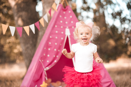Laughing baby girl celebrating birthday outdoors. Birthday party decorations. Happiness.