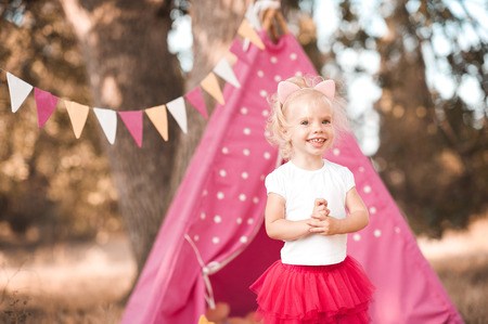 Laughing cute baby girl 2-3 year old celebrating birthday outdoors. Looking away. Wearing summer clothes: skirt and top. Childhood. Stock Photo