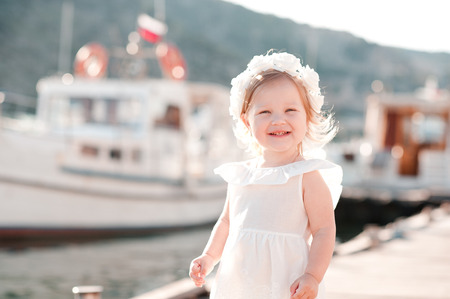 3 year old: Laughing baby girl 2-3 year old wearing stylish white dress outdoors. Smiling child. Childhood. Stock Photo