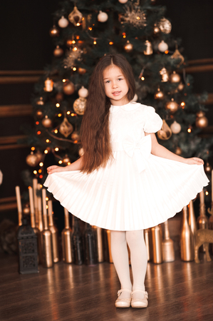 Beautiful kid girl 4-5 year old wearing white stylish dress standing in room over Christmas tree. Looking at camera. Merry Christmas. Holiday season.  Stock Photo
