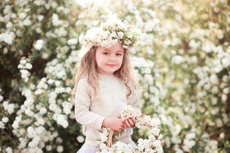 Cute kid girl 3-4 year old wearing stylish clothes and holding basket with flowers outdoors. Childhood. Looking at camera.